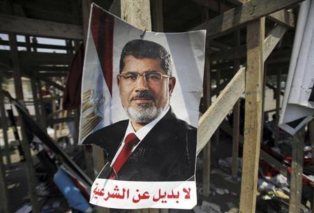 A poster of Egypt's President Mohamed Mursi reads, ''No substitute for the legitimacy'' is seen near members of the Muslim Brotherhood after night clashes with anti-Mursi around Cairo University and Nahdet Misr Square in Giza, on the outskirts of Cairo July 3, 2013. REUTERS/Amr Abdallah Dalsh