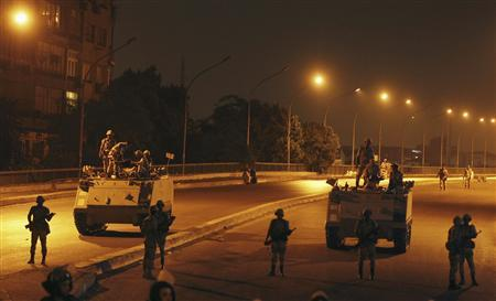 Army soldiers take their positions on the bridge towards members of the Muslim Brotherhood and supporters of Mursi standing guard around Cairo University and Nahdet Misr Square in Giza, on the outskirts of Cairo July 3, 2013. REUTERS/Louafi Larbi