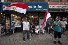 Men wave Egyptian flags on the street in the Queens borough of New York, July 3, 2013. REUTERS/Carlo Allegri