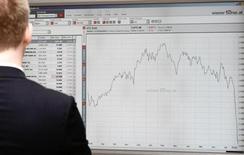Человек смотрит на экран с котировками на фондовой бирже в Вене 9 августа 2011 года. Европейские рынки акций начали торги четверга ростом вслед за Уолл-стрит и Азией, однако подъем, вероятно, будет ограничен из-за политической неопределенности в Португалии и Египте. REUTERS/Heinz-Peter Bader