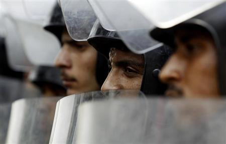 Riot police stand with their shields as members of the Muslim Brotherhood and supporters of ousted Egyptian President Mohamed Mursi protest in front of Egypt's Constitutional Court during the swearing in ceremony of Adli Mansour as the nation's interim president in Cairo July 4, 2013. REUTERS/Amr Abdallah Dalsh
