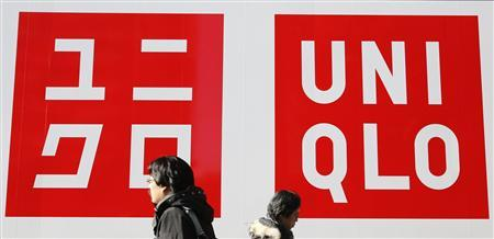 Passersby walk past the logos of Fast Retailing's Uniqlo casual clothing store in Tokyo in this January 10, 2013 file photo. Uniqlo, owned by Japan's Fast Retailing Co is opening two stores in Bangladesh,a favourite low-cost sourcing hub for many international retailers but a country where, until now, they have not sold their clothes. REUTERS/Toru Hanai/Files