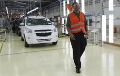 Marcos Purty, president director of General Motors Indonesia, stands next to new Chevrolet Spin MPVs during the official launch of the GM plant in Bekasi, on the outskirts of Jakarta February 19, 2013. Picture taken February 19, 2013. REUTERS/Enny Nuraheni
