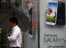 Мужчина с зонтом проходит мимо рекламного объявления смартфона Samsung Galaxy S4 в Сеуле 4 июля 2013 года. Samsung Electronics Co Ltd ждет роста прибыли во втором квартале на 47 процентов до рекордных 9,5 триллиона вон ($8,3 миллиарда). REUTERS/Kim Hong-Ji
