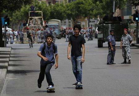 Two youths on skateboards pass by a police officer and a soldier securing a street they have closed off, where anti-Hezbollah activists had earlier held a protest, in Beirut June 9, 2013. REUTERS/ Jamal Saidi
