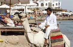 A bedouin walks with his camel in front of tourists while offering camel rides, in the Red Sea city of Dahab, Sinai, October 6, 2012. REUTERS/Asmaa Waguih