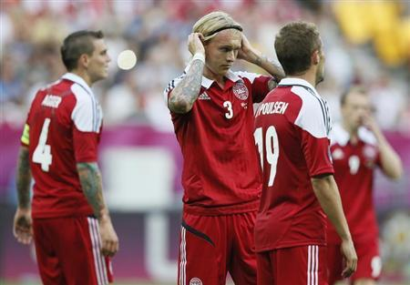 Denmark's Simon Kjaer (C) and Jakob Poulsen react after conceding Portugal's second goal during their Group B Euro 2012 soccer match at the New Lviv stadium in Lviv June 13, 2012. REUTERS/Michael Dalder