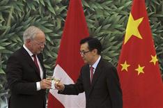 Chinese Commerce Minister Gao Hucheng (R) toasts with Swiss Economy Minister Johann Schneider-Ammann in front of the national flags of Switzerland (L) and China after signing a free-trade agreement at China's Ministry of Commerce in Beijing July 6, 2013. REUTERS/China Daily