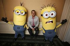 """Actor Steve Carell poses with two life-size minion characters while promoting his upcoming movie """"Despicable Me 2"""" in Los Angeles, California June 14, 2013. REUTERS/Mario Anzuoni"""