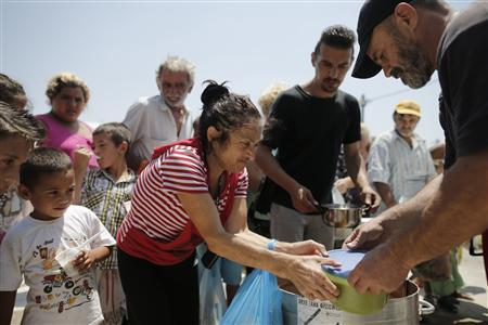People queue to receive food at a soup kitchen organised by a group called ''O Allos Anthropos'', or ''The Fellow Man'', outside the church of Agios Sozon in the suburb of Acharnes northwest of Athens July 7, 2013. REUTERS/John Kolesidis