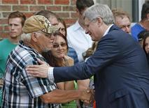 Canada's Prime Minister Stephen Harper shakes hands with people at the Polyvalente Montignac, the school sheltering the people who were forced to leave their houses after the explosion, in Lac Megantic, July 7, 2013. REUTERS/Mathieu Belanger