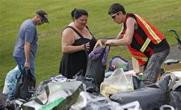 A volunteer gives clothes to a woman who's been evacuated from her home at the Polyvalente Montignac, the school sheltering the people who were forced to leave their houses after the explosion, in Lac Megantic, July 7, 2013. REUTERS/Mathieu Belanger