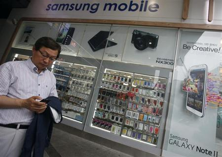 A man uses his mobile phone in front of a Samsung mobile shop in Seoul July 4, 2013. REUTERS/Kim Hong-Ji