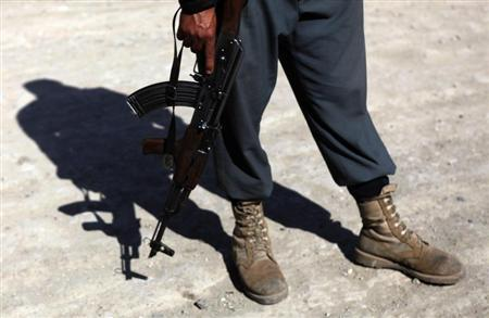 An Afghan policeman with a weapon stands at the site of a suicide attack in Kabul July 2, 2013. Taliban insurgents including a suicide bomber in a truck killed six people in the attack on a foreign logistics and supply company in Kabul on Tuesday. REUTERS/Mohammad Ismail
