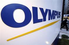 A man passes a logo of Japan's Olympus Corp outside the company showroom in Tokyo December 21, 2012. REUTERS/Yuriko Nakao