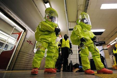 Emergency personnel stand in front of a subway train before a re-enactment of a hazardous situation in the lower level of the Bay Subway station that is no longer in use in Toronto January 25, 2011. REUTERS/Mark Blinch