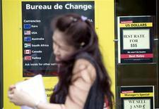 Женщина проходит мимо пункта обмена валют в Лондоне 4 июля 2013 года. Рост доллара к корзине мировых валют приостановился, но аналитики считают, что тенденция к росту сохранится благодаря ожиданиям сокращения стимулирующей программы ФРС. REUTERS/Neil Hall