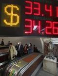Курс рубля к доллару на вывеске обменного пункта в московском метро 4 июня 2012 года. Рубль подрос при открытии биржевой сессии вторника, отразив позитивные тенденции глобальных рынков, динамика может быть ограничена ожиданиями завтрашней публикации протоколов последнего заседания Комитета по открытым рынкам ФРС США и пятничного совета директоров ЦБР по вопросам денежно-кредитной политики. REUTERS/Maxim Shemetov