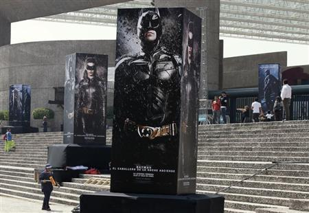 Posters of the film ''The Dark Knight Rises'' are displayed outside as people wait for the midnight premiere of the final instalment of Christopher Nolan's Batman trilogy at the National Auditorium in Mexico City July 23, 2012. REUTERS/Henry Romero
