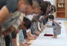 A child walks near members of the Muslim community attending midday prayers at Strasbourg Grand Mosque in Strasbourg on the first day of Ramadan July 9, 2013. REUTERS/Vincent Kessler