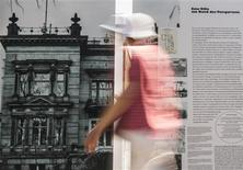 """A woman walks past an information board showing a picture of the villa that served as the headquarters for Nazi Germany's """"euthanasia"""" programme in Berlin, July 9, 2013. REUTERS/Thomas Peter"""