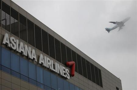 Aircraft flies over the head office of Asiana Airlines in Seoul July 7, 2013. REUTERS/Kim Hong-Ji