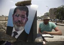 Un partidario del ex presidente egipcio Mohamed Mursi lee el Corán junto a la plaza Raba El-Adwyia en El Cairo, jul 11 2013. Los gobernantes interinos de Egipto aplaudieron el jueves las declaraciones del Departamento de Estado estadounidense que describieron al Gobierno del derrocado líder Mohamed Mursi como no democrático, esperando que fueran una señal de que Washington no cortará su ayuda anual de 1.500 millones de dólares. REUTERS/Amr Abdallah Dalsh