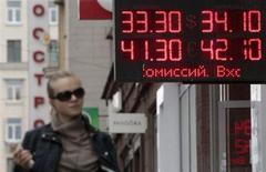 Женщина проходит мимо пункта обмена валют в Москве 1 июня 2012 года. Рубль незначительно снизился к бивалютной корзине утром пятницы перед советом директоров ЦБ по вопросам денежно-кредитной политики, также подешевел к доллару США и подрос к евро, отразив текущее незначительное ослабление пары евро/доллар на форексе. REUTERS/Sergei Karpukhin