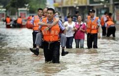 """Полицейский переносит мужчину на затопленной улице в Чэнду 9 июля 2013 года. Китай и Тайвань ждут в пятницу прихода тайфуна """"Соулик"""", тогда как в результате проливных дождей в Поднебесной погибли или пропали без вести уже более 200 человек. REUTERS/China Daily"""