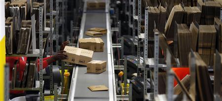 A worker packs boxes at Amazon's logistics centre in Graben near Augsburg December 17, 2012. REUTERS/Michael Dalder
