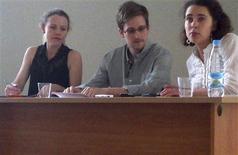 """Бывший сотрудник американских спецслужб Эдвард Сноуден (в центре) и Сара Харрисон из WikiLeaks (слева) разговаривают с правозащитниками в московском аэропорту Шереметьево 12 июля 2013 года. Беглый сотрудник спецслужб США Эдвард Сноуден в пятницу впервые предстал перед отобранной им самим публикой в транзитной зоне московского аэропорта и повторил просьбу о временном убежище в России на пути в Латинскую Америку, на что Кремль напомнил об условиях: прекратить """"антиамериканскую деятельность"""". REUTERS/Human Rights Watch/Handout"""