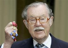 Veteran British travel broadcaster Alan Whicker holds his CBE (Commander of the Order of the British Empire) after receiving the honour from Britain's Queen Elizabeth at Buckingham Palace, London in this March 22, 2005 file photo. REUTERS/Kirsty Wigglesworth/Pool/Files