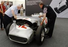 Bonhams employees replace the cover of the Mercedes-Benz W196 einsitzer ahead of its auction by Bonhams at the Goodwood Festival of Speed at Goodwood near Chichester in southern England July 11, 2013. REUTERS/Luke MacGregor