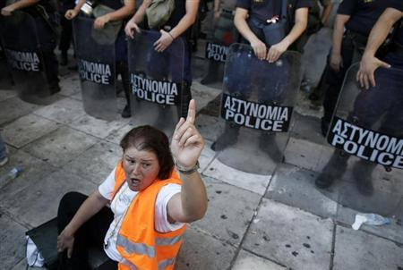 A municipal worker shouts slogans in front of riot police outside the Interior Ministry during a rally against public sector reforms in Athens July 8, 2013. REUTERS/John Kolesidis