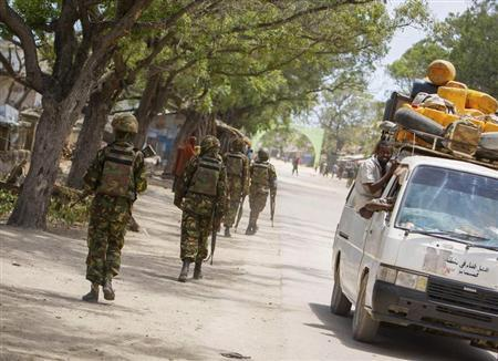 Soldiers, who are serving with the Kenyan Contingent of the African Union Mission in Somalia (AMISOM), patrol along a street as a commuter taxi passes by in the centre of the southern Somali port city of Kismayo, about 500 km (310 miles) south of Mogadishu in this October 7, 2012 handout photo taken and released by the African Union-United Nations Information Support Team. REUTERS/AU-UN IST PHOTO/Stuart Price/Handout