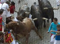An unidentified 23-year-old Australian woman (C, only her brown hair is visible in between the heads of the two bulls, with the white t-shirt) falls in between bulls after getting gored by a Miura fighting bull during the last running of the bulls of the San Fermin festival in Pamplona July 14, 2013. REUTERS/Alex Zugaza