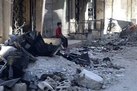 A boy sits on a damaged street filled with debris in Harasta area in Damascus July 14, 2013. REUTERS/ Mohamed Abdullah