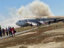 Passageiros são retirados do Boeing 777 após acidente na pista de pouso do aeroporto internacional de São Francisco, na Califórnia. A Asiana Airlines afirmou nesta segunda-feira que vai aprimorar o treinamento de pilotos para conduzir novos aviões, como parte de uma série de medidas tomadas após o acidente fatal. 6/07/2013 REUTERS/Eugene Anthony Rah/Handout via Reuters