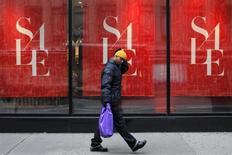 Homem com sacola de compras caminha em frente a uma loja em liquidação, em Nova York. As vendas no varejo nos Estados Unidos subiram menos do que o esperado em junho, ampliando os sinais de desaceleração no crescimento econômico, que podem servir de argumento contra a possibilidade de o banco central norte-americano começar a reduzir seu estímulo monetário ainda neste ano. 26/12/2012. REUTERS/Eduardo Munoz