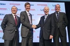 Executive chairman of Loblaw Companies Limited Galen G. Weston and Chair of the Board of Directors of Shoppers Drug Mart Holger Kluge (2nd R) shake hands, as President of Loblaw companies Limited Vicente Trius (R) and Shoppers Drug Mart CEO Domenic Pilla (L) look on during a news conference in Toronto, July 15, 2013. REUTERS/Mark Blinch