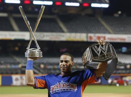 American League batter Yoenis Cespedes, of the Oakland A's, holds up the Home Run trophy and a belt after winning the Major League Baseball All-Star Game Home Run Derby in New York, July 15, 2013. REUTERS/Shannon Stapleton
