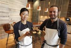 Chef and owner of the restaurant Hinoki & the Bird David Myers (R) poses with chef Kuniko Yagi in the restaurant with one of their signature dishes, hinoki scented black cod, sweet potatoes and pistachios in Los Angeles April 19, 2013. REUTERS/Fred Prouser
