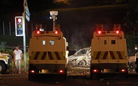 A man walks past a burnt out car on the shore road after the police came under attack from Loyalists throwing petrol bombs on the fourth night of unrest after an Orange Parade was blocked from marching past the Nationalist Ardoyne area in North Belfast July 16, 2013. REUTERS/Cathal McNaughton