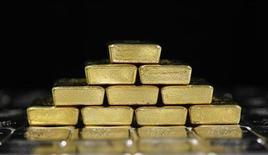 Золотые и серебряные слитки на заводе Oegussa в Вене 26 августа 2011 года. Цены на золото стабильны накануне выступления главы ФРС Бена Бернанке в Конгрессе. REUTERS/Lisi Niesner