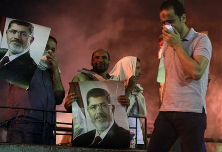 Supporters of deposed Egyptian President Mohamed Mursi carry posters of Mursi during clashes on the Sixth of October Bridge over the Ramsis square area in central Cairo July 15, 2013. REUTERS/Mohamed Abd El Ghany