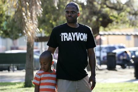 Jovan Blacknell (R) and his son Justice attend a peaceful protest of the acquittal of George Zimmerman for the 2012 shooting death of Trayvon Martin, in Los Angeles, California July 15, 2013. REUTERS/Jonathan Alcorn