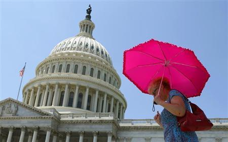 A woman holds an umbrella against the hot sun as she walks in front of the U.S. Capitol in Washington July 16 , 2013. REUTERS/Kevin Lamarque