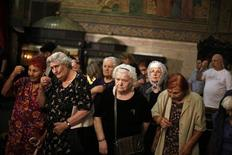 People pray during a funeral mass for Bishop Cyril at a cathedral in Varna, some 450 km (280 miles) northeast of Sofia July 11, 2013. REUTERS/Stoyan Nenov