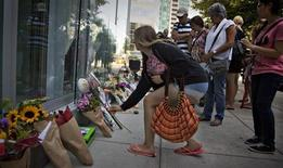 People gather at a small memorial to Canadian actor Cory Monteith outside the Fairmont Pacific Rim Hotel in Vancouver, British Columbia July 15, 2013. REUTERS/Andy Clark