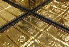 Слитки золота в магазине Ginza Tanaka в Токио 18 апреля 2013 года. Цены на золото снижаются, но по-прежнему близки к максимуму трех недель, тогда как доллар растет накануне выступления в Конгрессе председателя ФРС Бена Бернанке. REUTERS/Yuya Shino